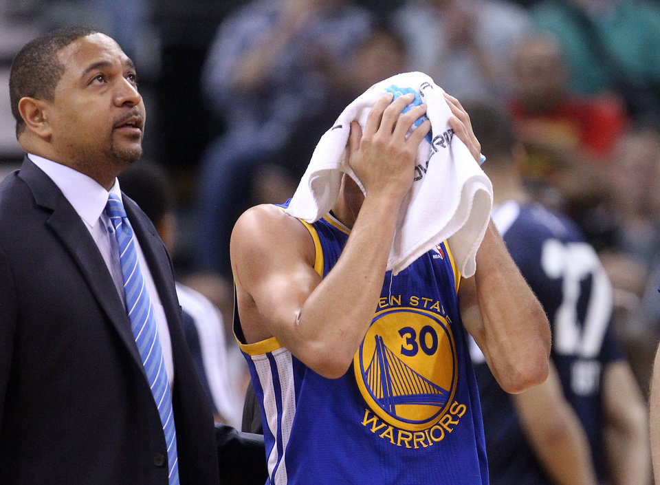 Photo - Golden State Warriors' Stephen Curry (30) holds a towel over his head as he walks off the court after being injured while his coach Mark Jackson looks on in the fourth quarter during an NBA basketball game Monday, Nov. 18, 2013, in Salt Lake City. (AP Photo/Rick Bowmer)