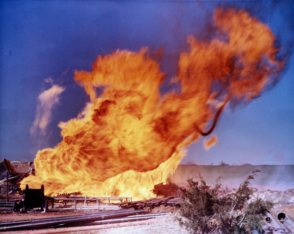 "Photo - (COLOR PHOTO)     ""Bright, orange flames from a wild gas well fire near El Reno soar skyward from a mass of charred, twisted pipe and drilling equipment.  The rig toppled but the crew escaped injury."" Staff COLOR photo by Al McLaughlin taken 3/10/71; photo ran in the 3/11/71 Daily Oklahoman.  ""Flames Out of Control""  ""El Reno Well Blazing""    ""A Sun Oil Co. gas development well burst into flames late Tuesday 10 miles southwest of El Reno and was burning out of control, a company spokesman said.    A Highway Patrol trooper said company officials were at the scene, 3 miles south of I-40, to determine what action was necessary to shut the well down.    The company spokesman said the well, C No. 1 Chiles, was located in the southwest Fort Reno Field in the Morrow Formation.     'There is no chance of the fire spreading to another well, and no real danger to the area,' he said.    A crew of three to five men had drilled to within 25 feet of the target depth of 11,200 feet when the well erupted, the company spokesman said.""....(From page 1 of the Wednesday, 3/10/71 Daily Oklahoman.)  File:  Oil Wells/Oil/State/Fires/El Reno/Sun Oil Co./C No. 1    Chiles"