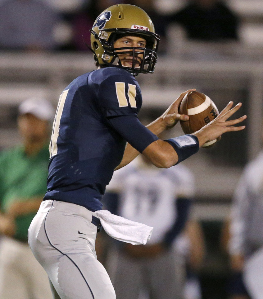 Photo - Heritage Hall's Connor McGinnis drops back to pass against Davis during their high school football game in Oklahoma City, Friday, Sept. 20, 2013. Photo by Bryan Terry, The Oklahoman