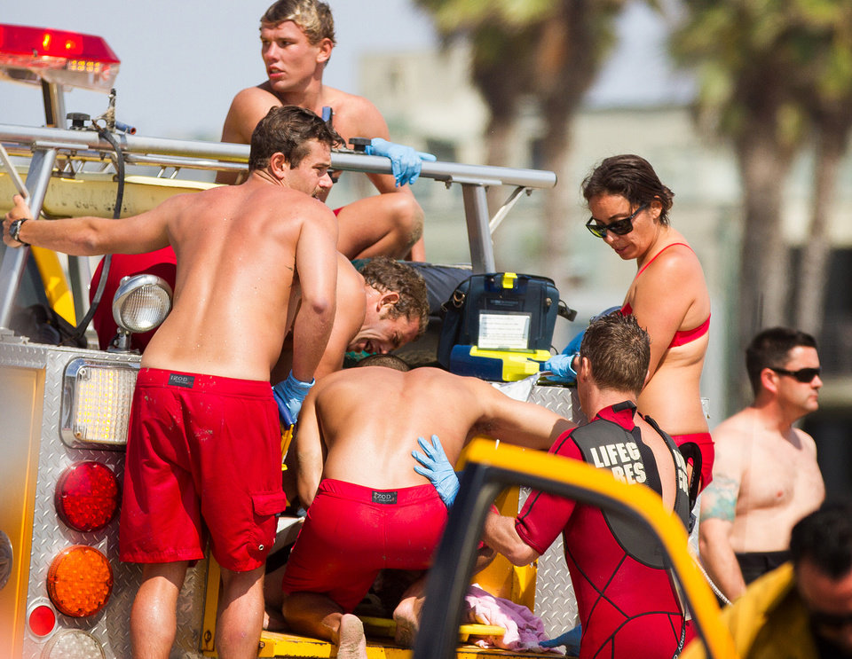 Photo - Lifeguards assist a person who was in the water Sunday, July 27, 2014 in Los Angeles, after authorities said lightning struck 14 people, leaving two critically injured, as rare summer thunderstorms swept through Southern California. (AP Photo/Steve Christensen)