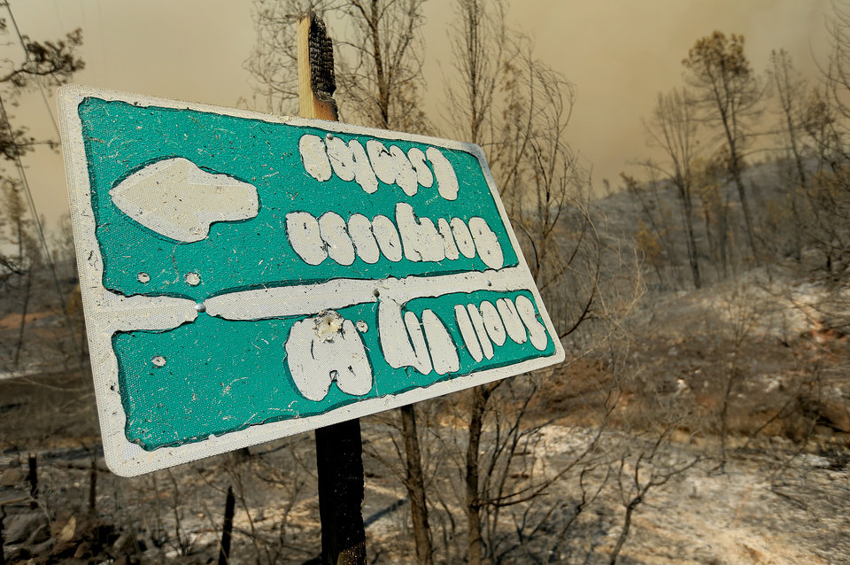 Photo - A sign, melted in the intense heat of the Butts Fire, gives arrows for Snell Valley Road and Berryessa Estates, Wednesday, July 2, 2014, near Middletown Calif. By early evening, the Butts Fire in remote Pope Valley grew to 3,800 acres from 3,200 acres, said Daniel Berlant, a spokesman for the California Department of Forestry and Fire Protection. The blaze is not threatening any major vineyards, Berlant and a spokeswoman for a vintners association said.  (AP Photo/Santa Rosa Press Democrat, Kent Porter)