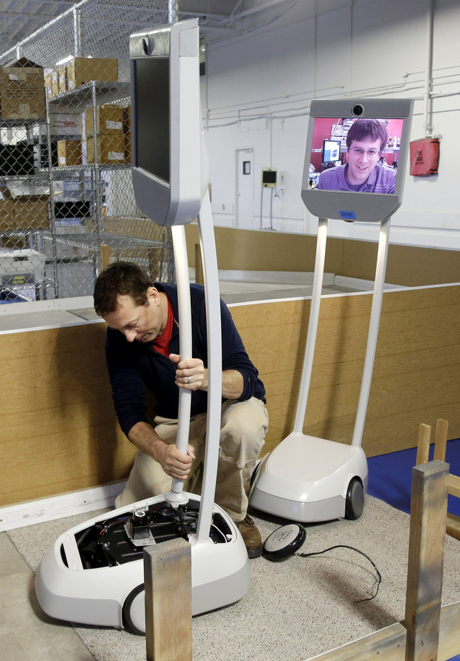 Engineer Christian Carlberg tests the Beam, a remote presence system,  through an obstacle course with the help of fellow engineer Dallas Goecker, top right on screen, communicating remotely from Seymour, Ind., at Suitable Technologies in Palo Alto, Calif., Wednesday, Dec. 12, 2012. More employees are working from home, but there's still no substitute for actually being at the office. Enter the Beam. It's a roving computer screen _ with video cameras, microphones and speakers _ that stands five feet and rides on motorized wheels. (AP Photo/Marcio Jose Sanchez)