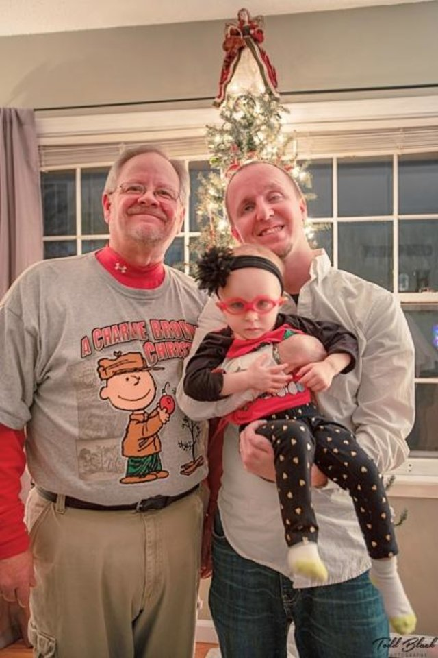 Photo -  Cameron Black holds his daughter, Addelyn, standing next to his father, Todd, last Christmas. The Blacks share a newfound bond over Sooner football. [Photo provided]