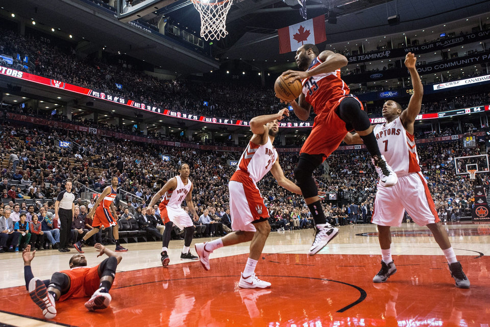 Photo - Washington Wizards' Trevor Booker, center right, takes a pass from the grounded John Wall, left, in front of the Toronto Raptors defense during first half NBA basketball action in Toronto, Thursday, Feb. 27, 2014. (AP Photo/The Canadian Press, Chris Young)