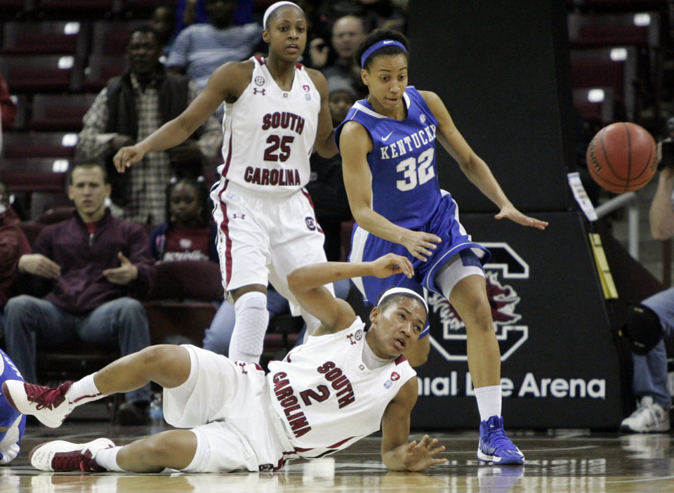 Photo - Kentucky's Kastine Evans (32) goes for the loose ball as South Carolina's Ieasia Walker (2) falls to the court and Tiffany Mitchell (25) watches during the first half of their NCAA college basketball game, Thursday, Jan. 24, 2013, in Columbia, S.C. (AP Photo/Mary Ann Chastain)