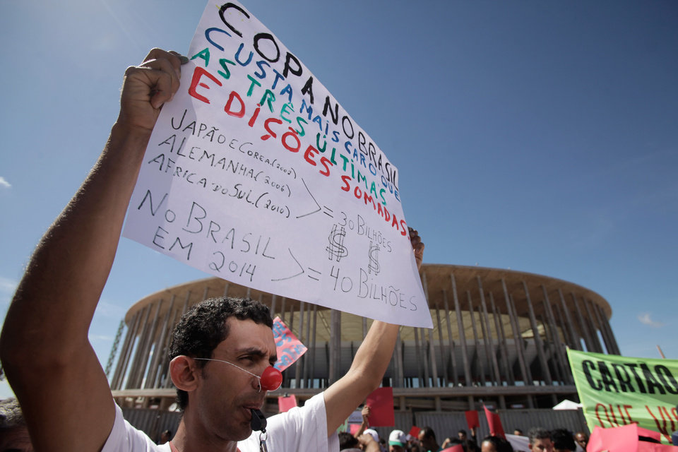 Photo - A demonstarator holds up a poster that reads in Portuguese;