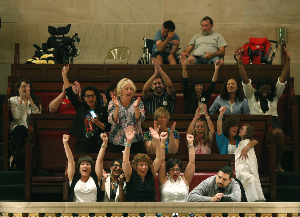 Photo - People in the gallery celebrate after the Senate voted to legalize medical marijuana at the Capitol on Friday, June 20, 2014, in Albany, N.Y.   The 49-10 approval follows the 113-13 vote earlier Friday by the Assembly for the compromise among legislative leaders and Gov. Andrew Cuomo. That will make New York the 23rd state to legalize, but the drug won't be available in New York for at least 18 months while regulations are written and five state-approved producers and distributors are chosen.  (AP Photo/Mike Groll)