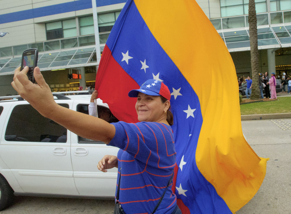 Cira Rodriguez of Miami, poses for a picture holding a Venezuelan flag before she waits in line to vote at the New Orleans Ernest Morial Convention Center, in New Orleans, Sunday, Oct. 7, 2012. Hundreds of Venezuelans living in the U.S. streamed into New Orleans on Sunday to cast ballots in the presidential election in their homeland, many of them determined to end the 13-year reign of Hugo Chavez. With the country's consulate in Miami closed, thousands of Venezuelans traveled by bus, car and plane to cast their votes at the consulate in New Orleans. (AP Photo/Matthew Hinton)