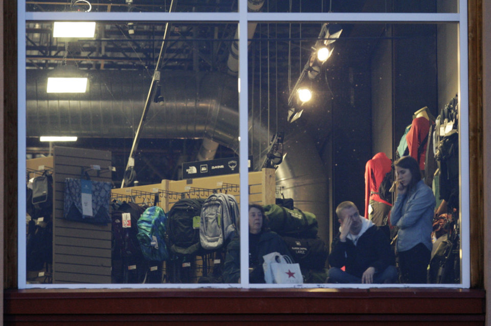 Photo - Mall workers and shoppers wait to be cleared to leave REI at Clackamas Town Center in Portland, Ore., where a shooting occurred Tuesday, Dec. 11, 2012. A gunman opened fire at the suburban Portland shopping mall Tuesday, killing two people and wounding another as people were doing their Christmas shopping, authorities said. (AP Photo/The Oregonian, Thomas Boyd)