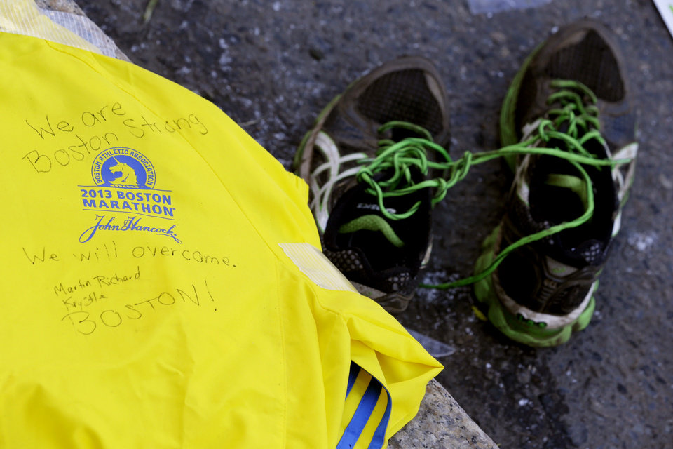 Photo - A message is written on a volunteer's jacket near running shoes at a makeshift memorial on Boylston Street near the blast site of the Boston Marathon explosions, Thursday, April 18, 2013, in Boston. The city continues to cope following Monday's explosions near the finish line of the marathon. (AP Photo/Julio Cortez)