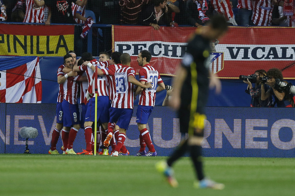 Photo - Atletico's Koke, obscured, celebrates his goal with team mates during the Champions League quarterfinal second leg soccer match between Atletico Madrid and FC Barcelona at the Vicente Calderon stadium in Madrid, Spain, Wednesday, April 9, 2014. (AP Photo/Andres Kudacki)