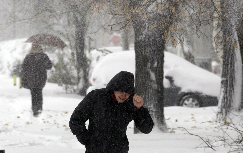 People walk through the snow covered street during the snow storm in Belgrade, Serbia, Sunday, Dec. 9, 2012. Freezing temperatures and heavy snowfall have killed at least 5 people and caused travel chaos across the Balkans. (AP Photo/Darko Vojinovic)