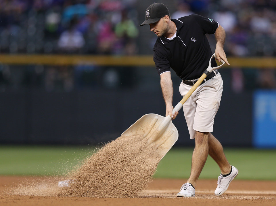 Photo - As a persistent rain falls, a Coors Feild groundskeeper uses a shovel to distribute absorbent material on the infield in the fourth inning of a baseball game between the Pittsburgh Pirates and the Colorado Rockies in Denver on Saturday, July 26, 2014. (AP Photo/David Zalubowski)