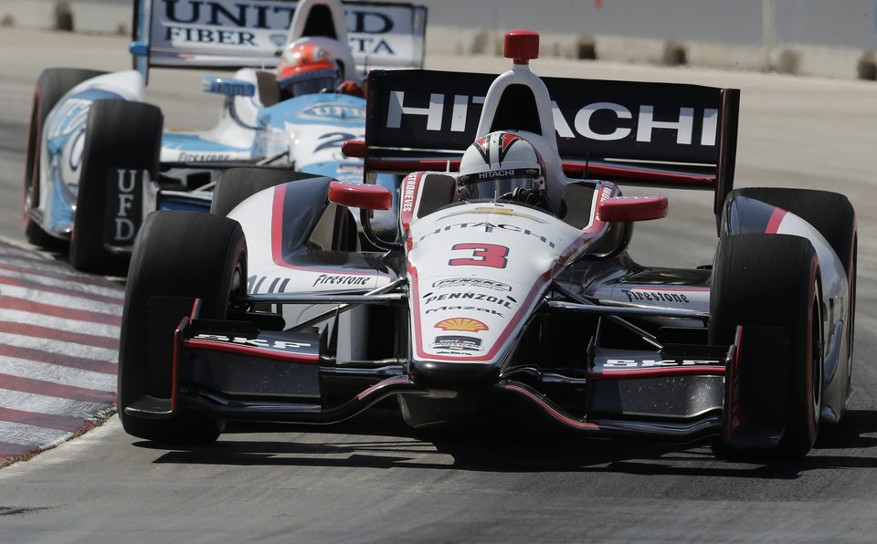 Photo - Helio Castroneves runs through turn one during the second race of the IndyCar Detroit Grand Prix auto racing doubleheader in Detroit Sunday, June 1, 2014. (AP Photo/Paul Sancya)