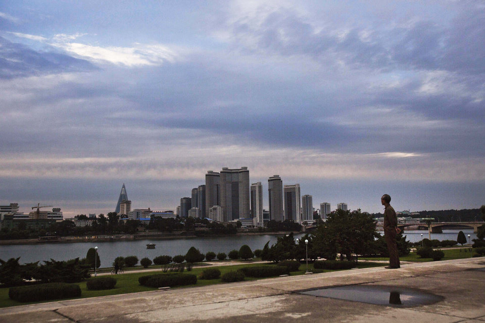 Photo -   In this Sept. 13, 2012 photo, a man looks across the river at central Pyongyang, North Korea. (AP Photo/David Guttenfelder)