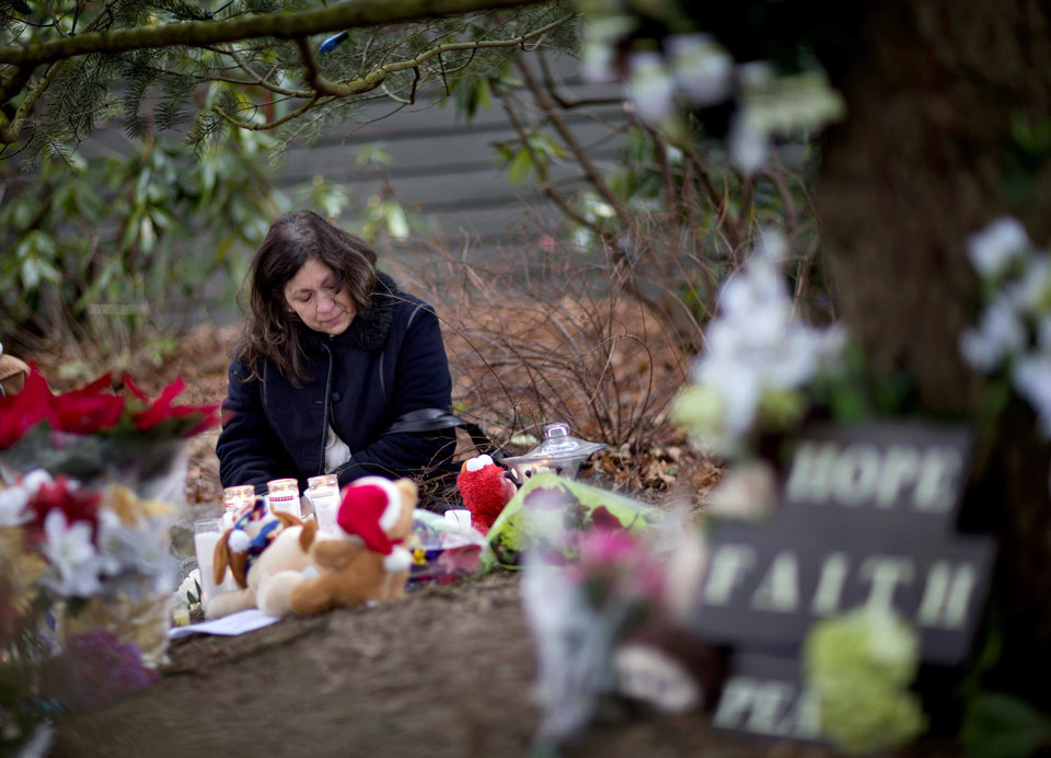 Photo - Dilma Steiner, of Newtown, Conn., visits a sidewalk memorial for the Sandy Hook Elementary School shooting victims, Sunday, Dec. 16, 2012, in Newtown, Conn. A gunman walked into Sandy Hook Elementary School in Newtown Friday and opened fire, killing 26 people, including 20 children. (AP Photo/David Goldman)