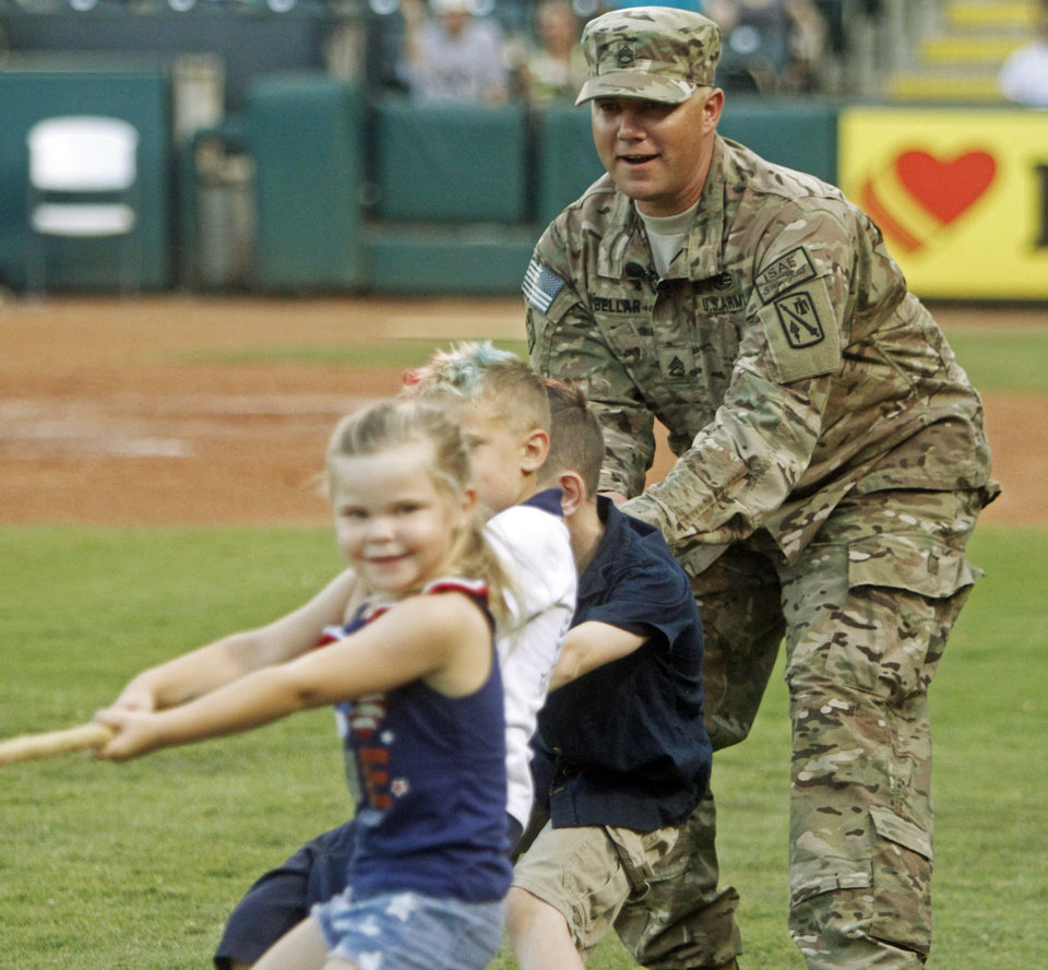 Photo - Staff sgt. Jason Bellar, surprises his kids during a game of tug-of-war after returning home after a nine month tour in Afghanistan during a minor league baseball game between the Oklahoma City Redhawks and the New Orleans Zephyrs at Chickasaw Bricktown Ballpark on July 8, 2014. Photo by KT King/The Oklahoman