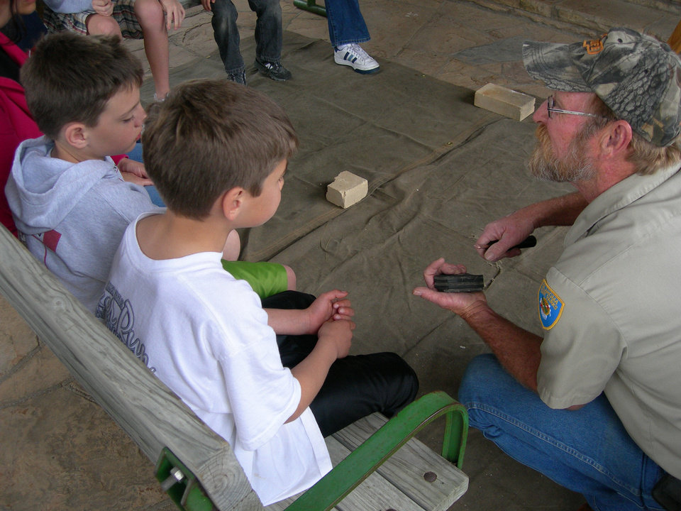 Photo - Two young guests learn a skill at a state park nature program. PHOTO PROVIDED