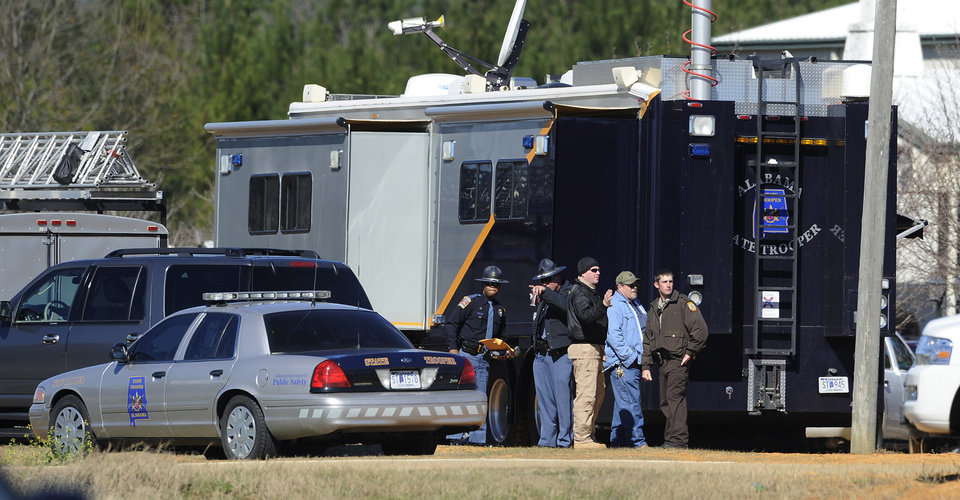 Photo - Law officers stand beside the Alabama State trooper mobile command post at the Dale County hostage scene in Midland City, Ala. on Thursday, Jan. 31, 2013. A gunman holed up in a bunker with a 6-year-old hostage has kept law officers at bay since the standoff began when he killed a school bus driver and dragged the boy away, authorities said. (AP Photo/Montgomery Advertiser, Mickey Welsh)