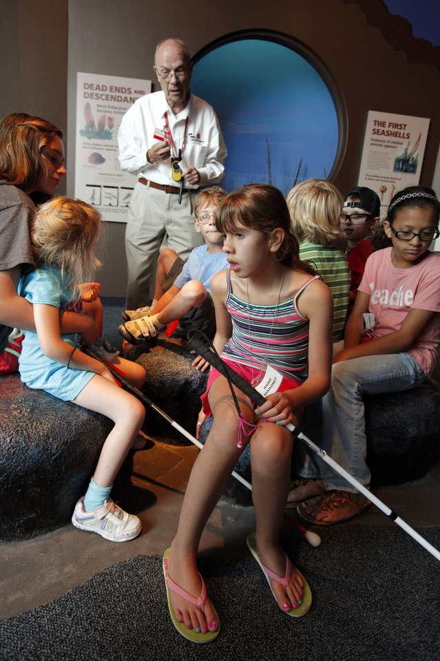Photo - Annie Mahoney, 8, of Tulsa, listens to docent Bill Miller Wednesday as visually impaired campers with Oklahomans Without Limits tour the Sam Noble Oklahoma Museum of Natural History. PHOTO BY STEVE SISNEY, THE OKLAHOMAN  STEVE SISNEY
