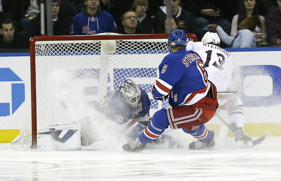 Photo - Columbus Blue Jackets' Cam Atkinson (13) scores on New York Rangers goalie Henrik Lundqvist (30), of Sweden, during the second period of an NHL hockey game, Monday, Jan. 6, 2014, in New York.  (AP Photo/Frank Franklin II)