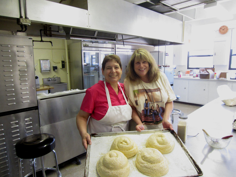 Emanuel Sisterhood members Debra Wolraich and Amy Settles show round challah dough ready for the oven during a recent sisterhood baking session at Emanuel Synagogue, 900 NW 47. Photo provided
