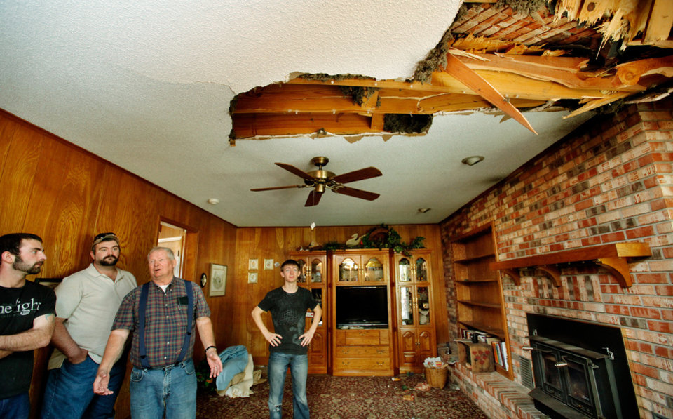Homeowner Joseph Reneau, third from left, shows friends the damage caused to his home\'s family room after the chimney toppled onto the roof, creating a large hole in the ceiling. An earthquake late Saturday night caused extensive damage to the two-story ranch style home of Joseph and Mary Reneau near the community of Sparks in Lincoln County. Contents inside their home were damaged earlier Saturday when a earthquake was struck the same area. The Reneaus have lived in their house for 25 years. Photo by Jim Beckel, The Oklahoman ORG XMIT: KOD