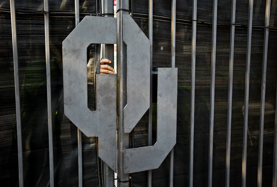 Photo - A security guard's hand keeps the gate closed before the start of the college football game between the University of Oklahoma Sooners (OU) and the Tulsa University Hurricanes (TU) at the Gaylord Family-Memorial Stadium on Saturday, Sept. 3, 2011, in Norman, Okla. 