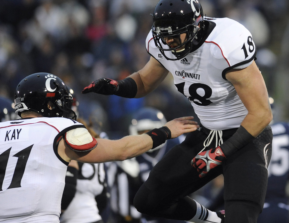 Photo - Cincinnati quarterback Brendon Kay, left, celebrates with Cincinnati tight end Travis Kelce, right, after Kelce's touchdown during the first half of an NCAA college football game at Rentschler Field in East Hartford, Conn., Saturday, Dec. 1, 2012. (AP Photo/Jessica Hill)
