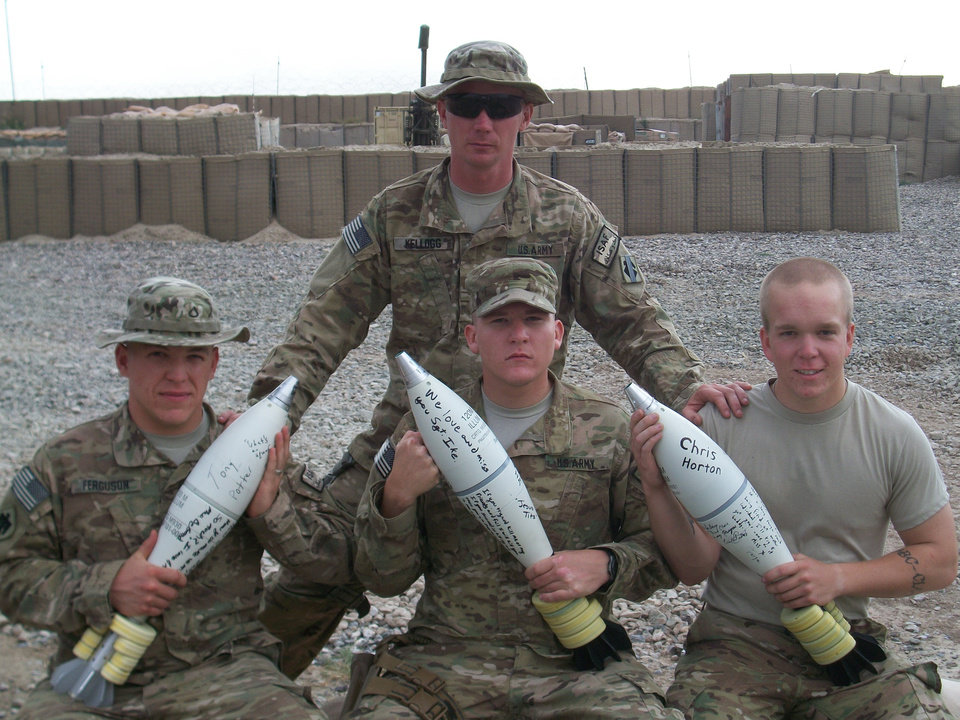 Staff Sgt. Duane Kellogg, rear, and Pfc. Matt Ferguson, left, Pfc. Maxx Robinson and Spc. Shane Cox pose at their forward operating base with mortar rounds bearing handwritten messages to their fallen comrades.