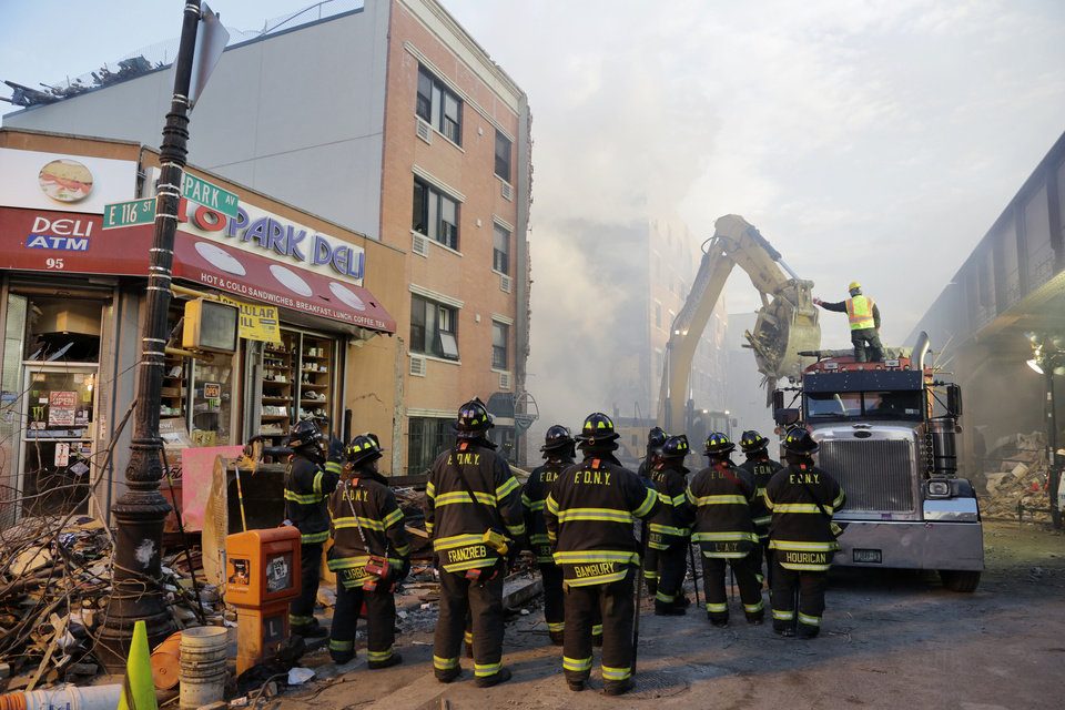 Photo - An excavator removes debris from the site of a building explosion, Thursday, March 13, 2014 in New York.  Rescuers working amid gusty winds, cold temperatures and billowing smoke pulled four additional bodies Thursday from the rubble of two New York City apartment buildings, raising the death toll to at least seven from a gas leak-triggered explosion that reduced the area to a pile of smashed bricks, splinters and mangled metal.  The explosion Wednesday morning in Manhattan's East Harlem injured more than 60 people.  (AP Photo/Mark Lennihan)