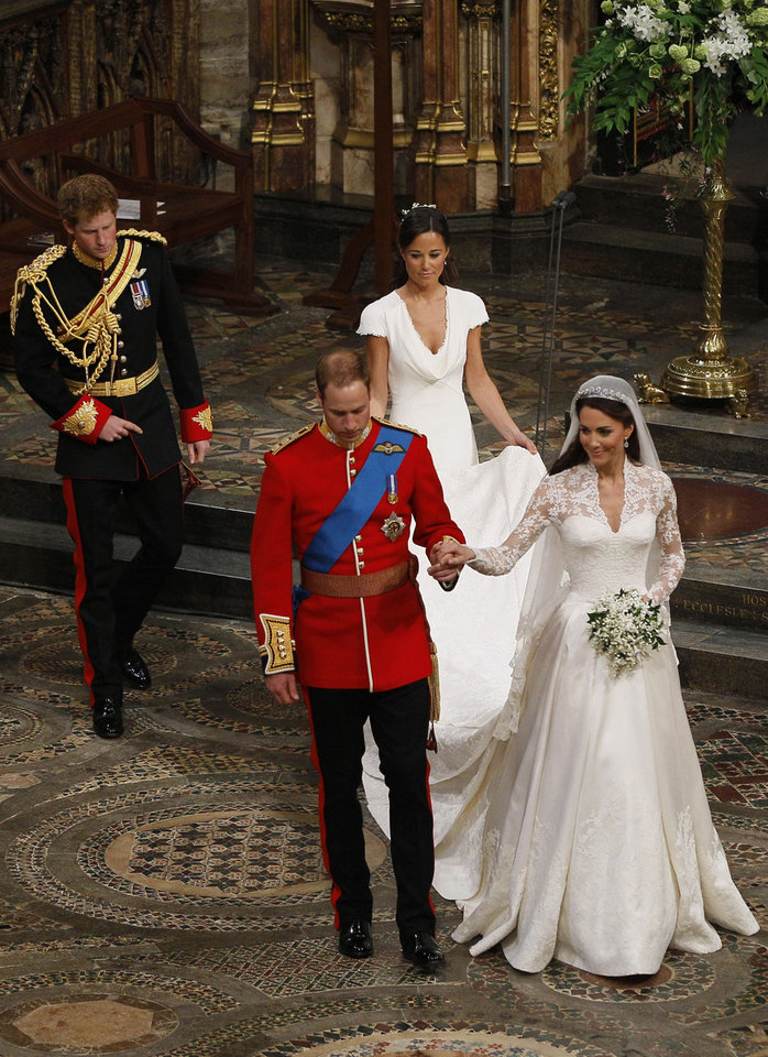 Photo - Britain's Prince William, foreground left, and his wife Kate, the Duchess of Cambridge, foreground right, walk hand in hand as Britain's Prince Harry, William's best man, back left, and maid of honour Philippa Middleton, back right, accompany them following their wedding service at Westminster Abbey in London, Friday, April 29, 2011. (AP Photo/Kirsty Wigglesworth, Pool) ORG XMIT: LKW104