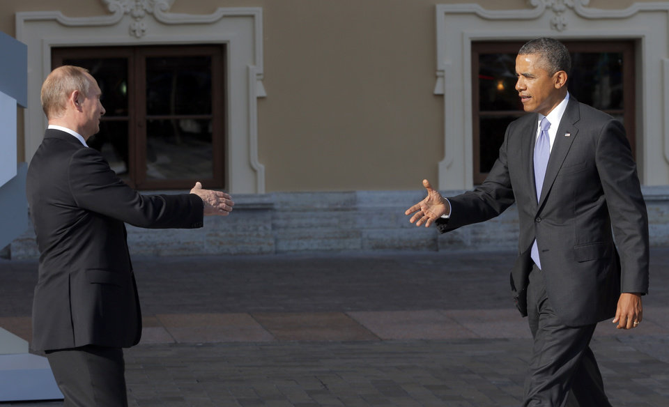 Photo - Russia's President Vladimir Putin, left, reaches out to shake hands with U.S. President Barack Obama during arrivals for the G-20 summit at the Konstantin Palace in St. Petersburg, Russia on Thursday, Sept. 5, 2013. The threat of missiles over the Mediterranean is weighing on world leaders meeting on the shores of the Baltic this week, and eclipsing economic battles that usually dominate when the G-20 world economies meet. (AP Photo/Dmitry Lovetsky)