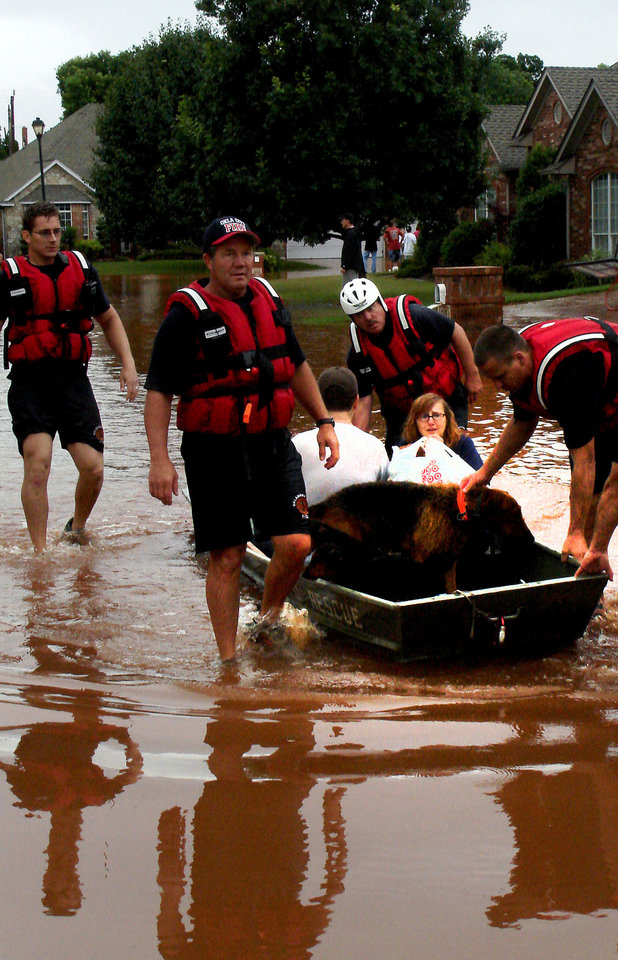 Photo - The Yele family is evacuated from their home in the Palo Verde subdivision in Edmond, Okla. Monday, June 14, 2010.  Photo by Jordon Shinn, The Oklahoman