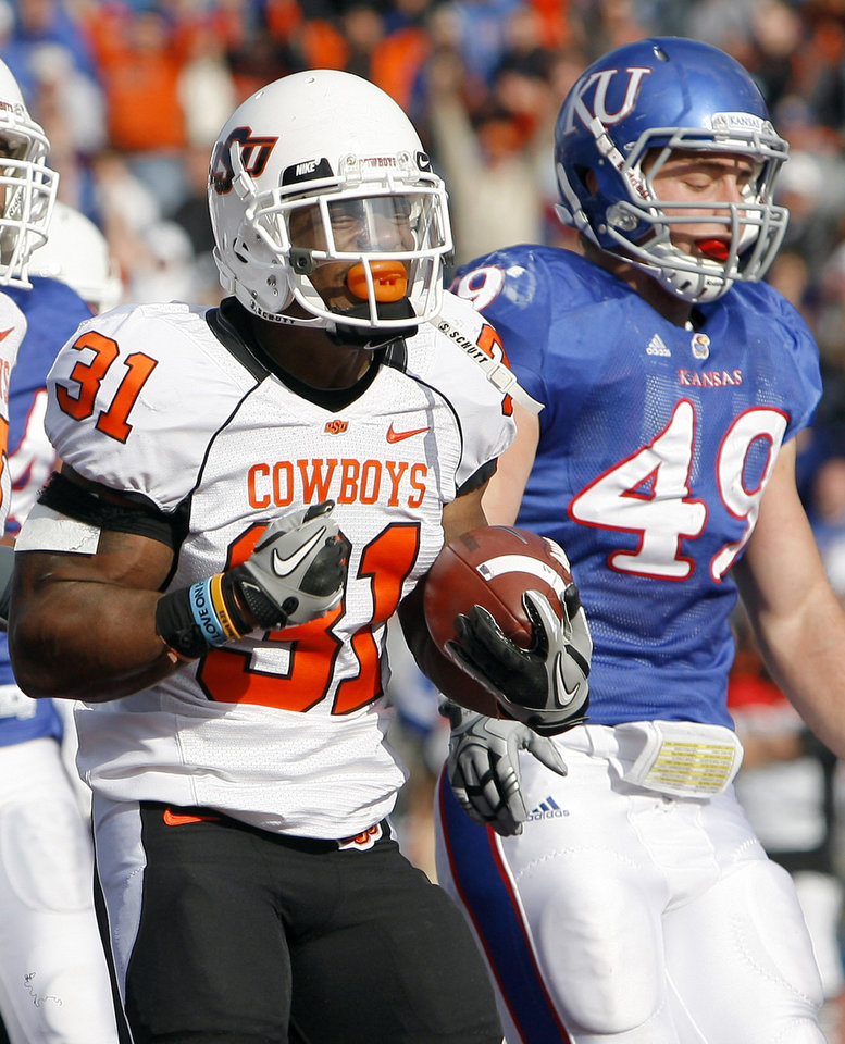 Photo - Oklahoma State's Jeremy Smith (31) celebrates a touchdown in front of Kansas' Drew Dudley (49) during the college football game between Oklahoma State (OSU) and Kansas (KU), Saturday, Nov. 20, 2010 at Memorial Stadium in Lawrence, Kan. Photo by Sarah Phipps, The Oklahoman