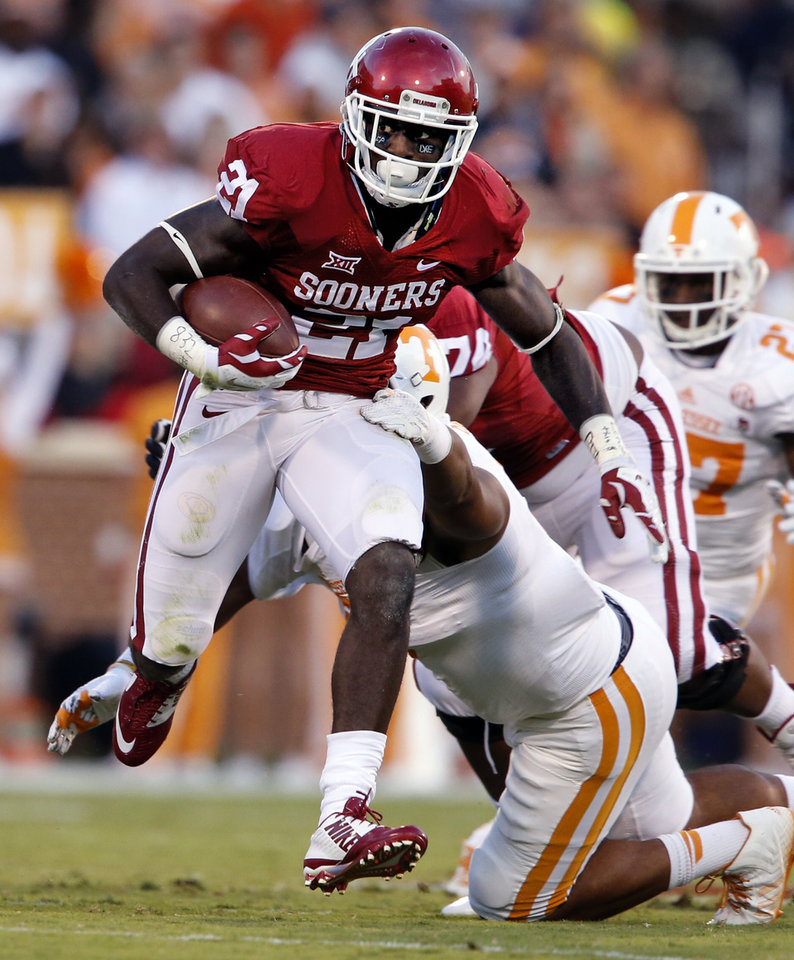 Photo - Oklahoma's Keith Ford (21) runs past the tackle of Tennessee's Derek Barnett (9) during a college football game between the University of Oklahoma Sooners (OU) and the Tennessee Volunteers at Gaylord Family-Oklahoma Memorial Stadium in Norman, Okla., on Saturday, Sept. 13, 2014. Photo by Steve Sisney, The Oklahoman