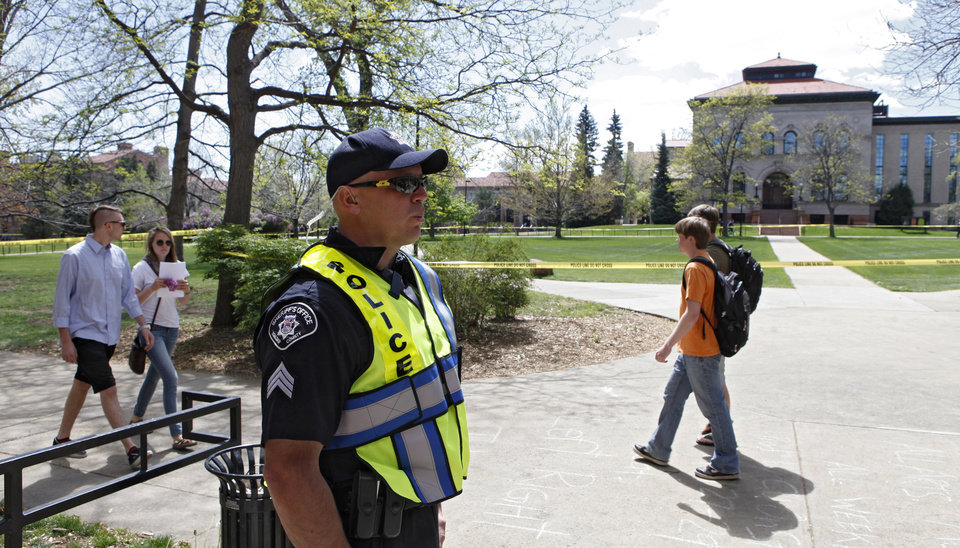 Photo -   Boulder County Sheriff Sgt. Jeff Goetz stands watch at the Norlin Quad at the University of Colorado in Boulder, Colo., on Friday, April 20, 2012. The university closed the area and the campus to prohibit an annual 420 marijuana smoke out. (AP Photo/Ed Andrieski)