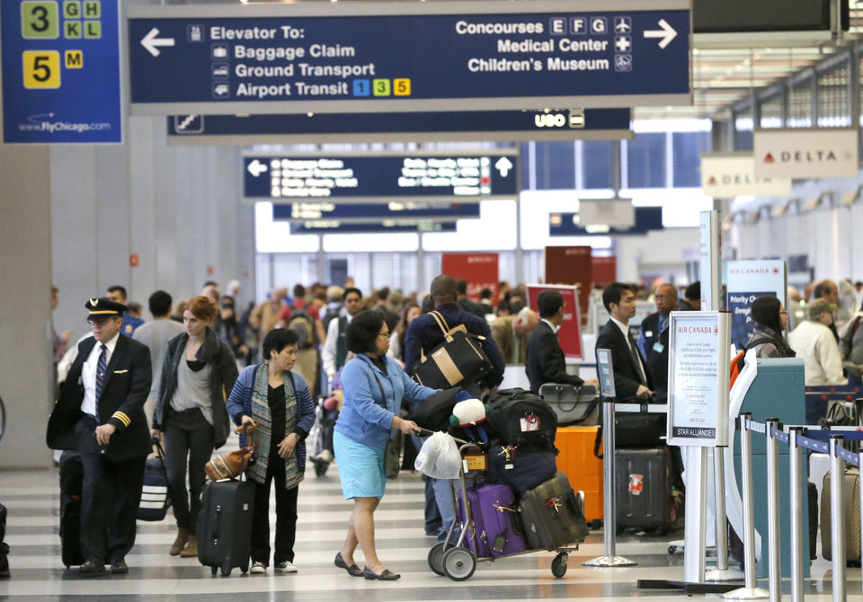 Photo - Passengers at O'Hare International Airport wait in a ticketing line Tuesday, May 13, 2014, in Chicago. Smoke in a regional radar facility forced a halt to all incoming and outgoing flights at both of Chicago's airports. The Federal Aviation Administration says all its personnel were evacuated from the Chicago Terminal Radar Approach Control, or TRACON, facility in suburban Elgin at around 11:30 a.m. Tuesday.(AP Photo/Charles Rex Arbogast)