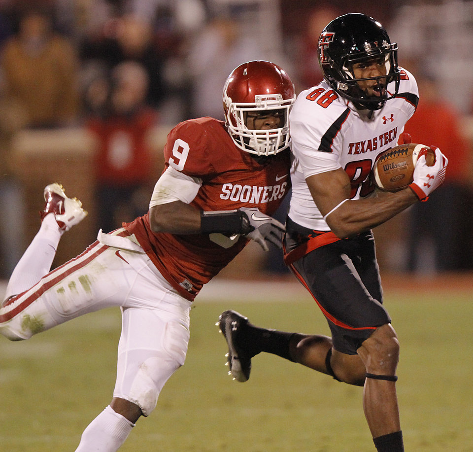 Photo - Texas Tech's Marcus Kennard (88) makes a catch in front of Oklahoma's Gabe Lynn (9) during the college football game between the University of Oklahoma Sooners (OU) and Texas Tech University Red Raiders (TTU) at the Gaylord Family-Oklahoma Memorial Stadium on Saturday, Oct. 22, 2011. in Norman, Okla. Photo by Chris Landsberger, The Oklahoman