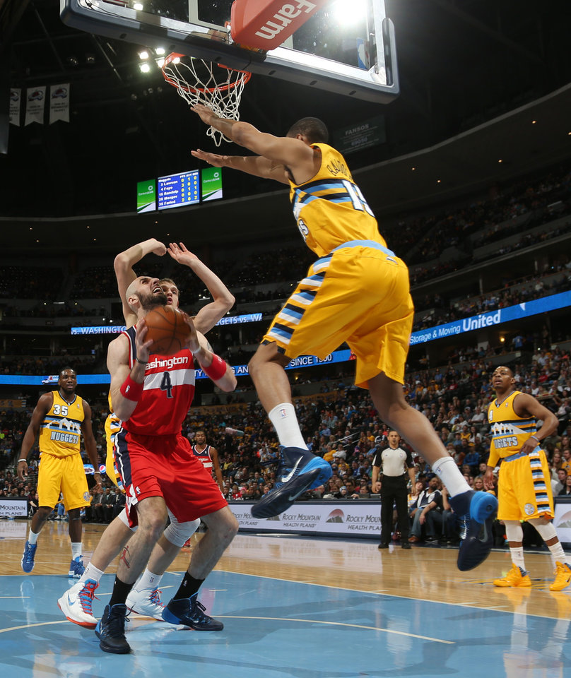 Photo - Washington Wizards center Marcin Gortat, front left, of Poland, goes up for shot as Denver Nuggets forward Anthony Randolph, right, and center Timofey Mozgov, back left, of Russia, cover in the first quarter of an NBA basketball game in Denver on Sunday, March 23, 2014. (AP Photo/David Zalubowski)