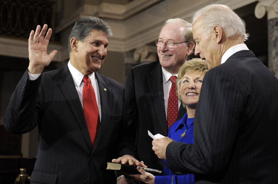 Photo - FILE - In this Jan. 3, 2013, file photo, Vice President Joe Biden administers the Senate Oath to Sen. Joe Manchin, D-W.Va., accompanied by his wife Gayle and Sen. Jay Rockefeller, D-W.Va., during a mock swearing in ceremony on Capitol Hill in Washington. Senate Democrats are approaching decision time on whether they can get Republican support for expanding background checks for firearms sales or will have to take the shakier path of pursuing the cornerstone of the gun control effort on their own. Democrats were to meet Tuesday, April 9, 2013, to discuss whether Manchin has been able to reach compromise with Republican Sen. Pat Toomey of Pennsylvania. (AP Photo/Cliff Owen, File)