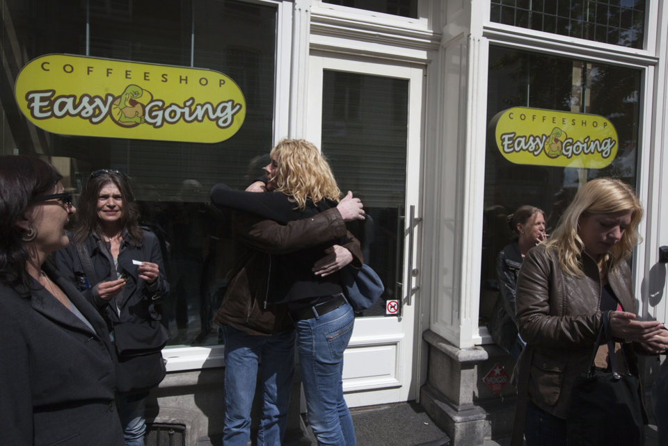 Photo -   People are seen outside closed coffeeshop Easy Going in Maastricht, southern Netherlands, Tuesday May 1, 2012. A policy barring foreign tourists from buying marijuana in the Netherlands goes into effect in parts of the country Tuesday, with a protest planned in the southern city of Maastricht. Easy Going first refused foreigners entry to provoke a complaint for discrimination, to later sell marijuana to foreigners to provoke a police reaction. Laster it closed its doors as all other coffeeshops in Maastricht were closed. (AP Photo/Peter Dejong)
