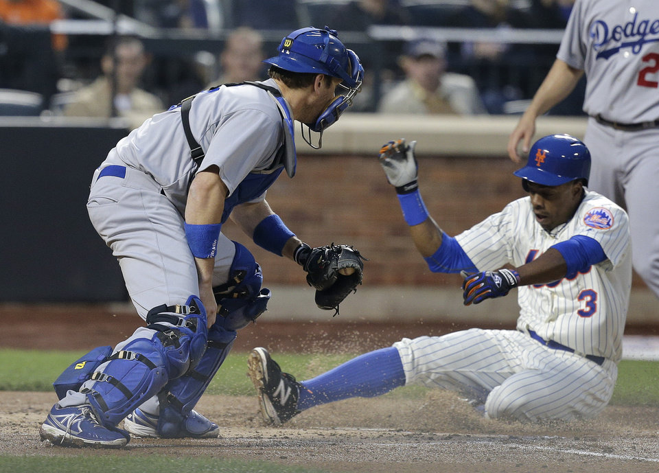 Photo - New York Mets Curtis Granderson (3) slides across home plate ahead of the tag from Los Angeles Dodgers catcher A.J. Ellis scoring on a sacrifice fly to right by Eric Campbell during the second inning of a baseball game, Thursday, May 22, 2014, in New York. (AP Photo/Julie Jacobson)