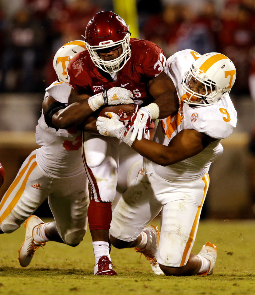 Photo - Oklahoma's Samaje Perine (32) carries and drags Tennessee's Jalen Reeves-Maybin (34) and Derek Barnett (9) along during the second half of a college football game between the University of Oklahoma Sooners (OU) and the Tennessee Volunteers at Gaylord Family-Oklahoma Memorial Stadium in Norman, Okla., on Saturday, Sept. 13, 2014. Photo by Steve Sisney, The Oklahoman