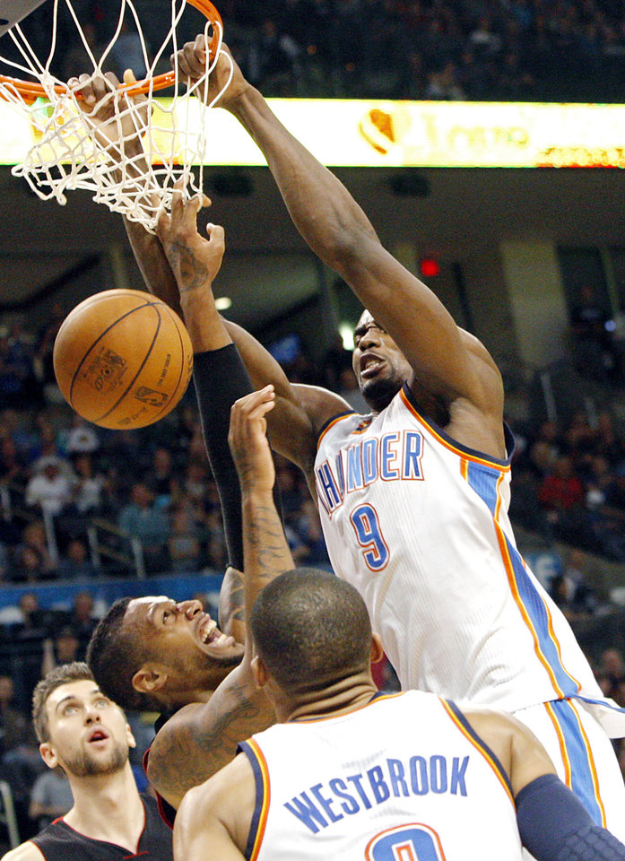 Oklahoma City's Serge Ibaka slams the ball in front of Toronto's James Johnson during the second half of their NBA basketball game at the OKC Arena in downtown Oklahoma City on Sunday, March 20, 2011. The Raptors beat the Thunder 95-93. Photo by John Clanton, The Oklahoman