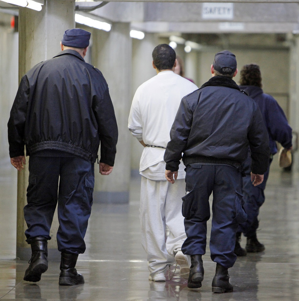 Photo - An inmate is escorted by two officers in H Unit at the Oklahoma State Penitentiary in McAlester, Okla., Wednesday, Dec. 7, 2011. Photo by Nate Billings, The Oklahoman