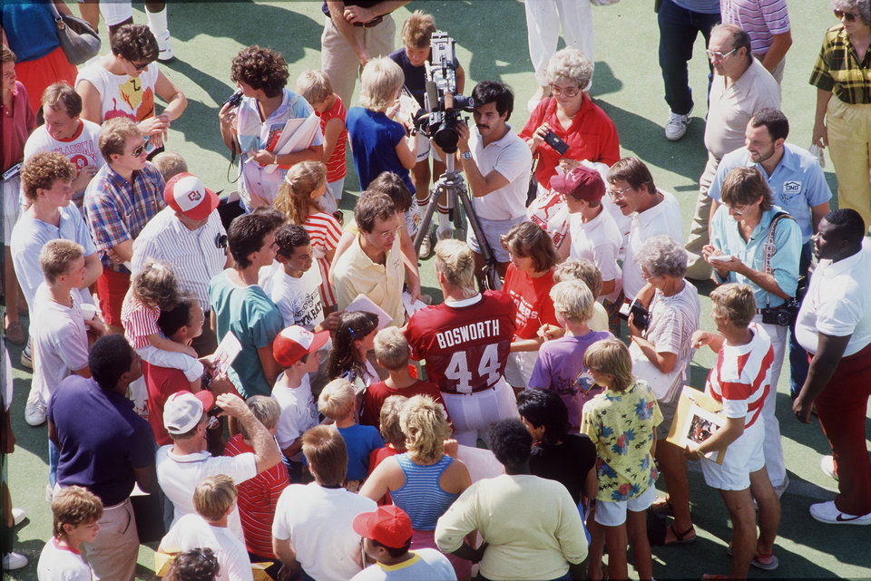 Photo - All-America linebacker Brian Bosworth was the center of attention during picture day at the University of Oklahoma back in 1986. Jason W. Taylor (in yellow Hawaiian shirt) and his buddy Adam Aiken (purple shirt) just hoped to get close to The Boz.