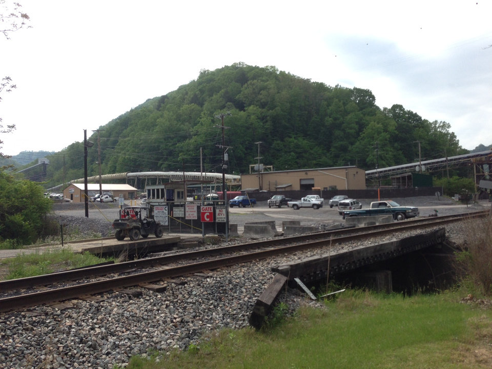 Photo - Vehicles are parked outside the Brody Mine No.1 in Wharton, W.Va., Tuesday May 13, 2014.  Two workers died after they were trapped as the ground failed at the West Virginia coal mine.  The ground failure occurred just about 8:45 p.m. Monday, trapping the workers, safety agency officials said.  The miners' bodies were recovered, and safety personnel were on the site of Brody Mine No. 1 in Boone County, about 50 miles south of Charleston.  Preliminary indications show that a coal burst was responsible, according to state officials and mine owner Patriot Coal. (AP Photo/Charleston Daily Mail, Marcus Constantino)