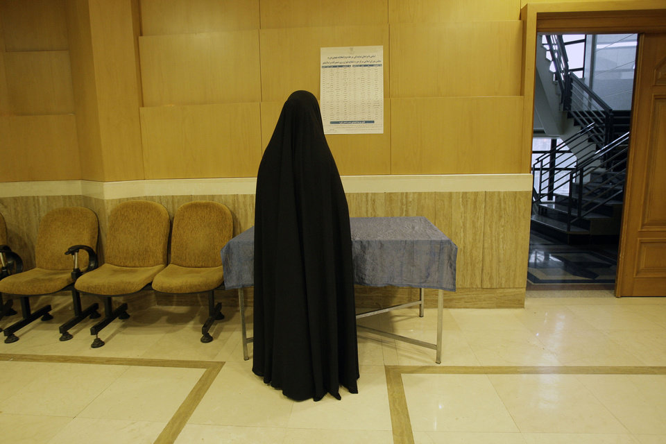 Photo -   A head-to-toe veiled Iranian woman checks the list of the candidates in the parliamentary runoff elections at a polling station in Tehran, Iran, Friday, May 4, 2012. The country has begun runoff elections for more than one-fifth of parliamentary seats. Friday's report says 130 hopefuls will compete for 65 seats in 33 constituencies including the capital Tehran with 25 undecided seats. (AP Photo/Vahid Salemi)