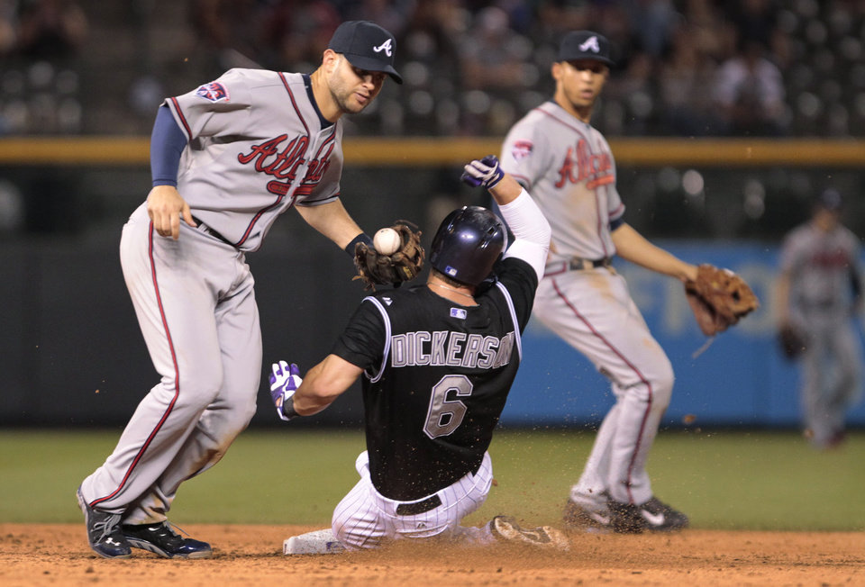 Photo - Atlanta Braves second baseman Tommy La Stella (7) drops the ball as Colorado Rockies' Corey Dickerson (6) steals second base in the eighth inning of a baseball game in Denver on Tuesday, June 10, 2014. (AP Photo/Joe Mahoney)